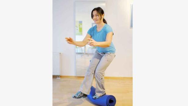 Einbein-Kniebeuge: Verbessert Beinkraft und Koordination. Noch Ski-spezifischer trainiert man auf einer zusammengerollten Matte