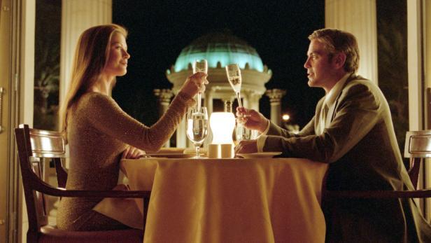 """2003 Universal Studios, Melinda Sue GordonAuf die Liebe - oder lieber doch nicht? Miles (George Clooney) versucht bei einem Essen, bei Marylin (Catherine Zeta-Jones) nicht nur den sprichw?rtlichen """"Fu§ in die T?r"""" zu bekommen. Honorarfrei - nur f?r diese"""