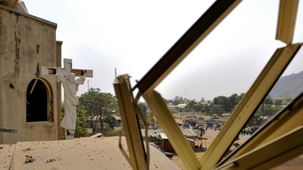 REUTERSA crucifix stands near a damaged structure at the scene of a car bomb explosion at  St. Theresa Catholic Church at Madalla, Suleja, just outside Nigerias capital Abuja, December 25, 2011. Islamist militant group Boko Haram said it planted bombs tha