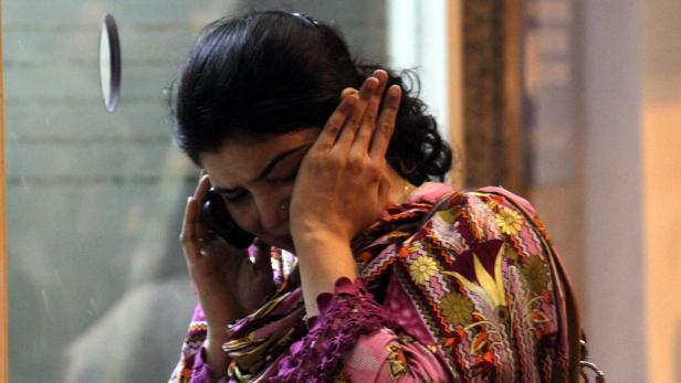 EPAepa03189931 A woman wipes her tears at Jinnah International Airport as others wait for updates on the fate of their relatives who were traveling on the Bhoja Air plane that crashed minutes before landing at Islamabad International Airport, in Karachi,