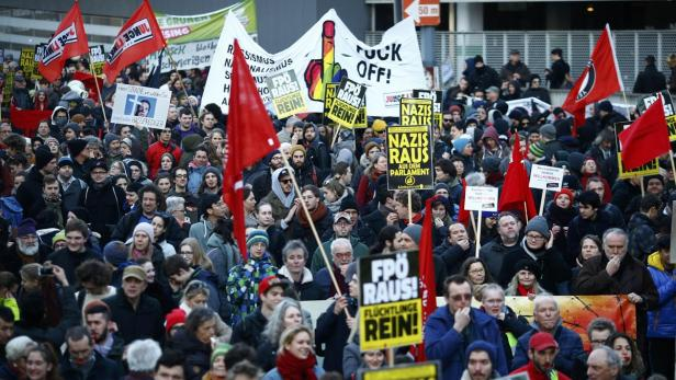 Protesters supporting a refugee home hold up banne