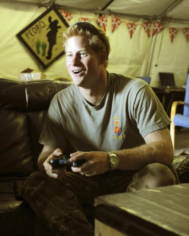 Britain's Prince Harry plays a computer soccer gam