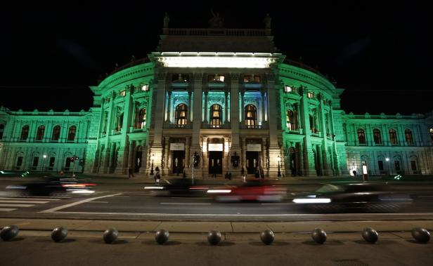 Some cars pass by Burgtheater which is lit in gree