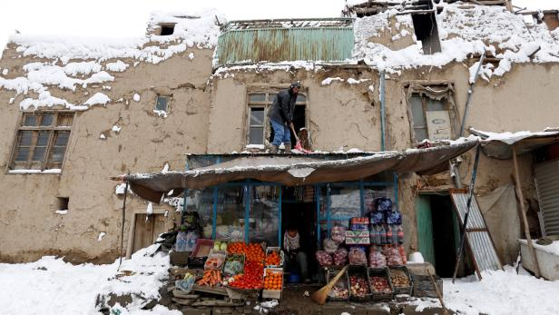 An Afghan man removes snow from his shop during a