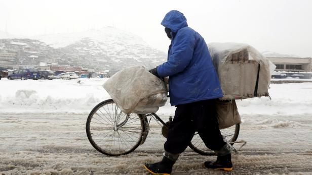 An Afghan man pushes his bicycle on a snowy day in