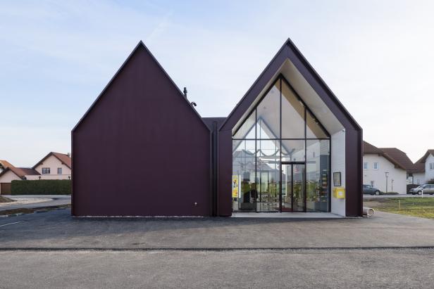 Das dunkelrote Metallkleid reicht vom Dach bis zum Fundament