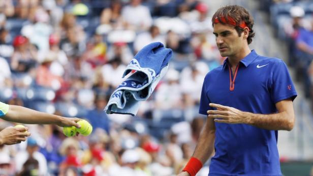 Roger Federer of Switzerland tosses his towel to a