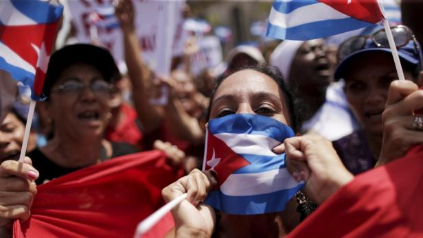 A government supporter kisses the Cuban flag as fe