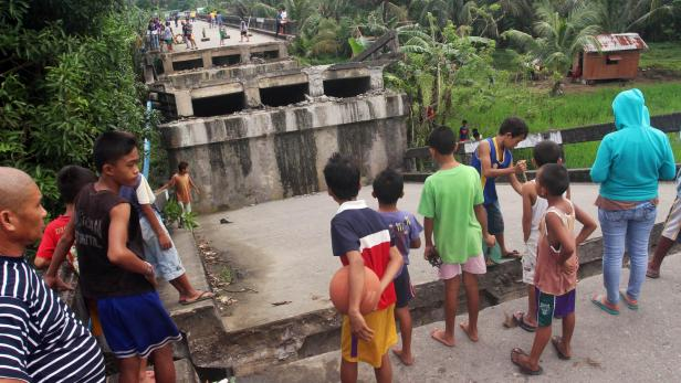 People look at the collapsed Anao-aon bridge after