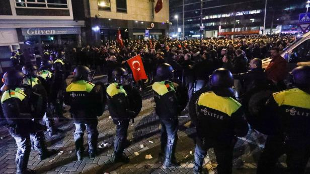 Demonstrators face Dutch riot police outside the T