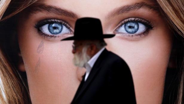 Zwei Welten: Ultra-Orthodoxer vor Werbeplakat.