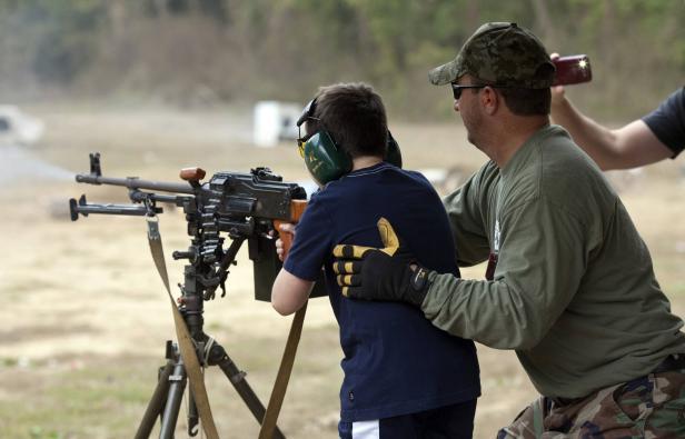 Cody Miller fires a machine gun with assistance from a range worker at Knob Creek Gun Range in West Point