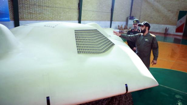 EPAepa03028461 An undated handout picture released by the official website of Irans Revolutionary Guards on 08 December 2011, shows Iranian Revolutionary Guard, General Amir-Ali Hajizadeh (2-R) looking at the US RQ-170 drone which reportedly crashed in ea