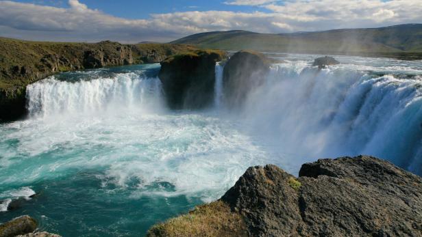 """Während der Rundreise zu Naturschönheiten besuchen Sie auch die bekanntesten Wasserfälle, unter anderem den 30 Meter breiten Godafoss, der auch """"Wasserfall der Götter"""" genannt wird."""
