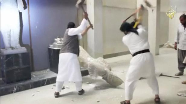 Men use sledgehammers on a toppled statue in a mus