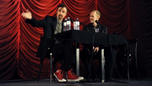 Boyle mit roten Turnschuhen im Gespräch mit Chris Cummins
