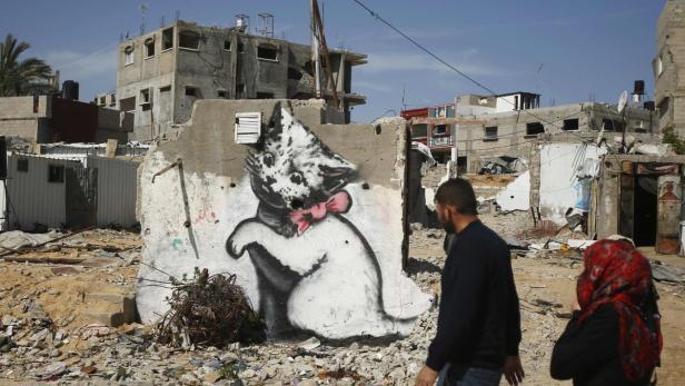 Palestinians walk past a mural of a kitten, presum