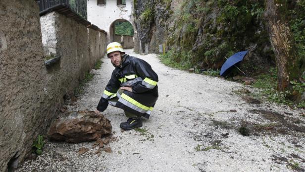 Ein Feuerwehrmann zeigt jenen Felsbrocken, der den Zehnjährigen erwischt hat.