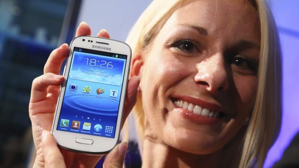 A model displays a Samsung 'Galaxy S3 mini' phone
