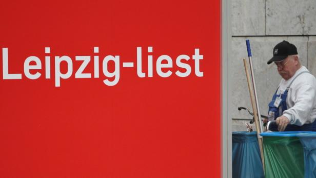 """dapdEin Gebaeudereiniger sammelt am Donnerstag (17.03.11) in Leipzig auf der Buchmesse in Leipzig Abfall neben einer Info-Box zum Lesefestival """"Leipzig liest"""". Am Donnerstag begann die Leipzger Buchmesse. Bis zum 20. Maerz 2011 zeigen 2.150 Aussteller aus"""