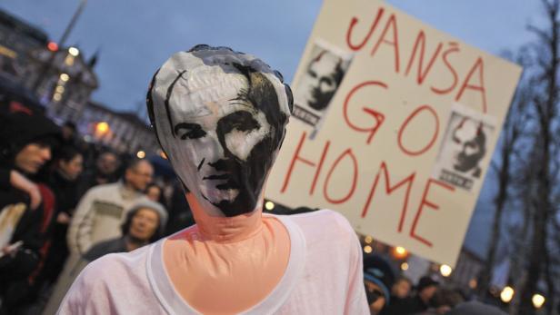 Demonstrators hold images of Slovenian Prime Minis