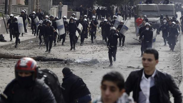 Riot police run towards protesters opposing Egypti