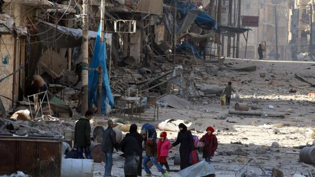 Syrians walk over rubble of damaged buildings, whi