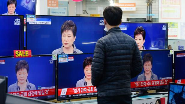A man watches television broadcast of a news repor
