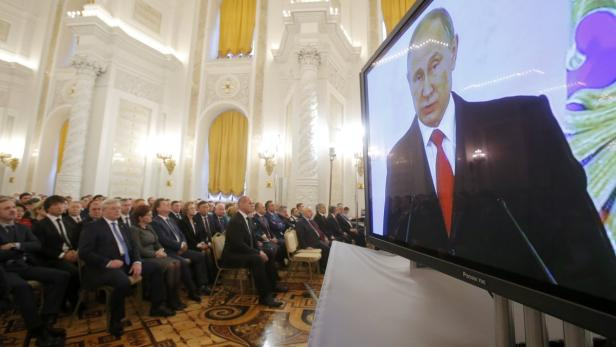 Russian President Putin is seen on screen during h