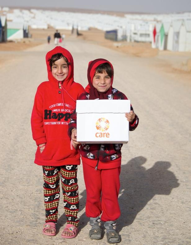 Two girls in refugee camp in Jordan with CARE pack…