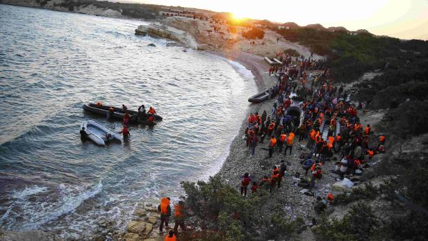 Refugees gather at a beach to try to sail off for