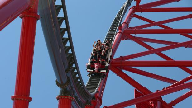 "People ride in the ""Red Force"" roller coaster duri"