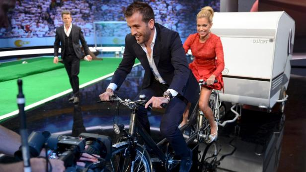 EPAepa03423797 German-Italian television host Markus Lanz (L) watches as Dutch soccer player Rafael Van Der Vaart (C) and his wife Sylvie (R) ride a bike during the 200th ZDF show Wetten, dass ..? (Bet that?), at the ISS Dome in Dusseldorf, Germany, 06 Oc
