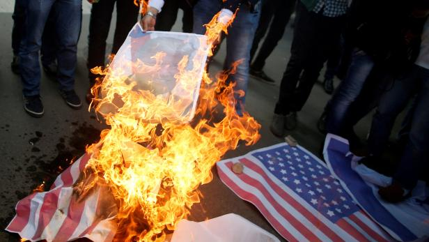 Palestinian protesters burn a poster depicting U.S