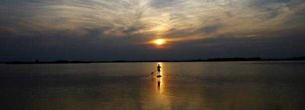 Kopie von A boy is silhouetted as he paddles on a stand up b