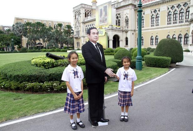 Children pose next to a cardboard cut-out of Thail