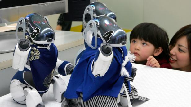 Girl and her mother look at Sony's robot dog AIBO