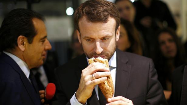 Frankreichs Präsident Macron genießt sein Baguette.
