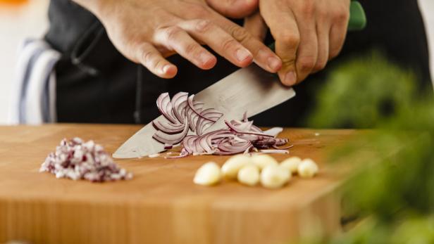 Chopping red onion on cutting board