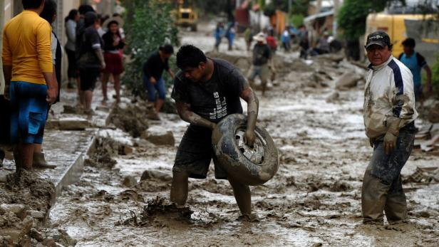 A man carries a tire during floods due to heavy ra