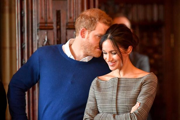 Britain's Prince Harry whispers to Meghan Markle a