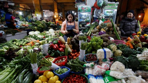Women sell vegetables at a market in Hanoi