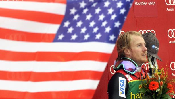 Ligety listens to the national anthem after the me