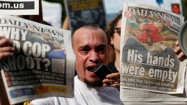 A man shows newspapers as people take part in a pr