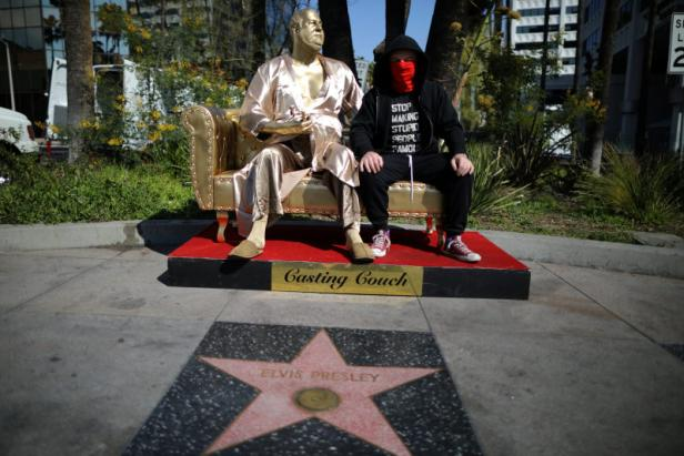Artist Plastic Jesus sits on his statue of Harvey