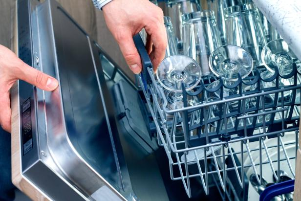 Man's hand opening dishwasher with clean utensils