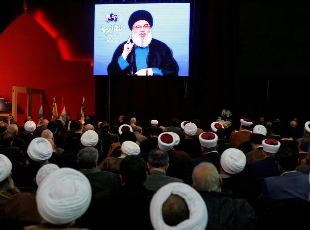 FILE PHOTO:Lebanon's Hezbollah leader Sayyed Hassan Nasrallah is seen on a video screen as he addresses his supporters in Beirut