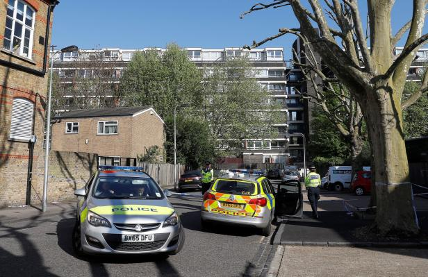 Police officers enforce a cordon at the scene where a teenager was found after being shot in London