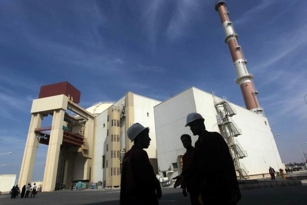 FILE PHOTO: Iranian workers stand in front of Bushehr nuclear power plant 1,200 km south of Tehran