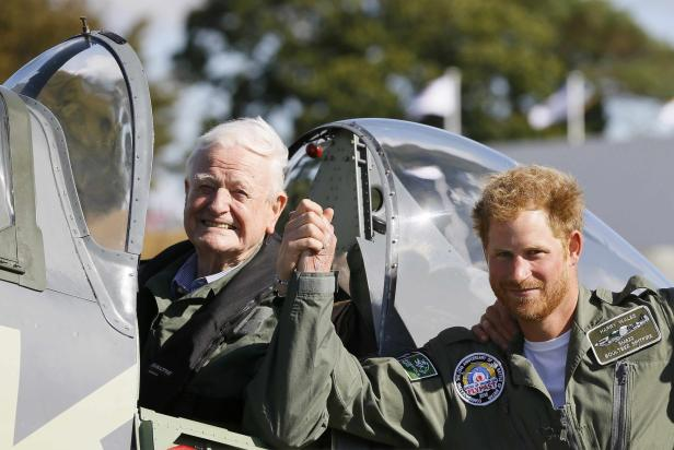 Britain's Prince Harry (R), poses for a photograph with veteran Tom Neill after he flew in a Spitfire during a Battle of Britain display at Goodwood Aerodrome in West Sussex, England